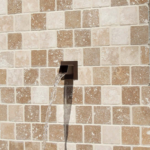 Square water spout mask displayed in fountain wall outdoor