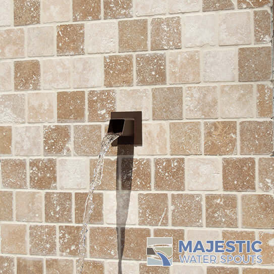Rust color Square water spout installed in tile wall outdoors