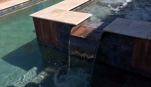 Copper brown patina water spillway installed in spa to pool water spillway