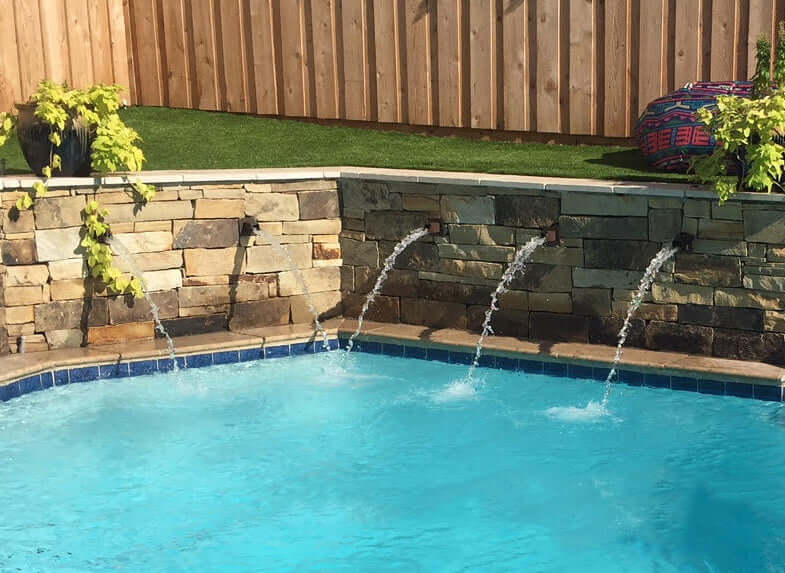 Rust color Square water spouts installed in pool fountain water feature outdoors