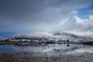 England, Cumbria, Lake District National Park. A winter view of Tewit Tarn (also spelt as Tewet Tarn) with a snow covered mountain (Blencathra) in the distance.