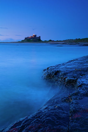 England, Northumberland, Bamburgh. Bamburgh Castle and the North Sea, viewed from Harkess Rocks.