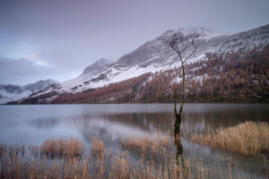 England, Cumbria, Lake District National Park. Snow covered mountains surround the lakeside at Buttermere in the Western Lake District.