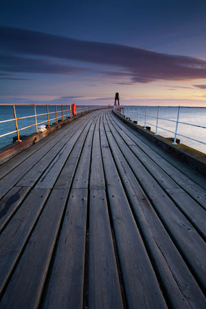 England, North Yorkshire, Whitby. One of the entrance piers of Whitby Harbour at dawn.