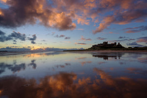 England, Northumberland, Bamburgh. The colours of dawn reflected on the wet, sandy beach at Bamburgh overlooked by Bamburgh Castle, located along the Northumberland Heritage Coast.