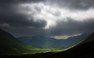 England, Cumbria, Lake District National Park. A break in the storm clouds illuminates the Mickleden and surrounding Langdale mountains, on the Cumbria Way.