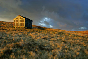 England, Cumbria, Lake District National Park.  The setting sun illuminates Lingy Hut, a welcome sight for hikers on the Cumbria Way track.