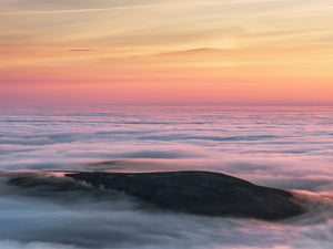 England, Northumberland, Northumberland National Park. Dawn viewed from the summit of The Cheviot looking at a Northumberland hill just above a lake of mist caused by a temperature (cloud) inversion.