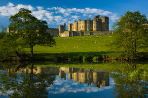 England, Northumberland, Alnwick. Alnwick Castle reflected in the still waters of the River Aln.
