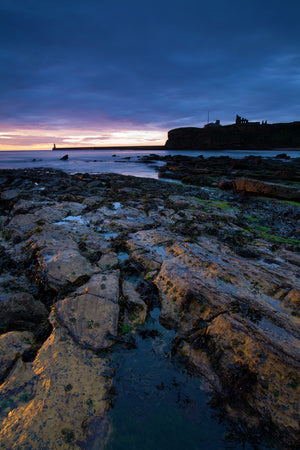 Sunrise over King Edward's Bay viewed from near Sharpness Point. The remains of Tynemouth Priory can be seen to the right.