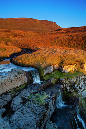 England, North Yorkshire, Yorkshire Dales National Park.  Last light on Horton Moor and a stream falling into a limestone sinkhole, with the distinctive peak of Pen-y-ghent in the distance.