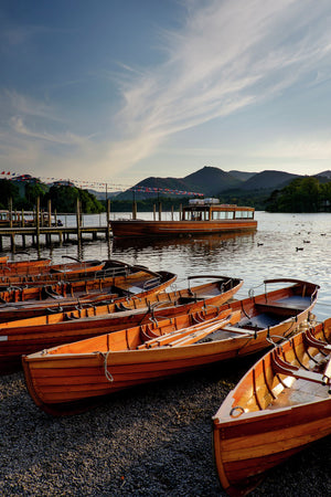 England, Cumbria, Lake District National Park. Wooden rowing boats and Derwent Water cruise ship moored at Keswick Jetty on Derwentwater