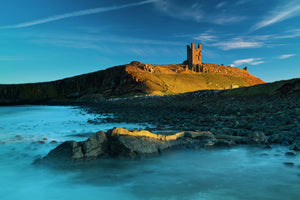 England, Northumberland, Embleton Bay. Last light on The Lilburn Tower, part of the remains of Dunstanburgh Castle, viewed from Embleton Bay.