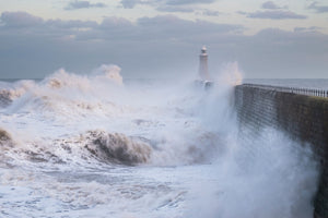 England, Tyne and Wear, Tynemouth. Waves crash at the mouth of the River Tyne, during a winter storm.