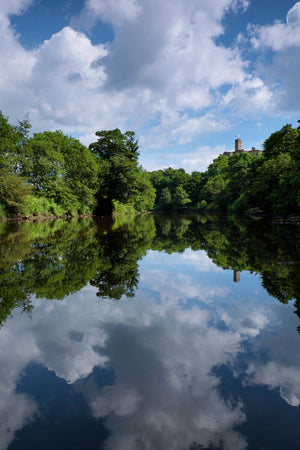 England, Northumberland, Warkworth. Warkworth Castle reflected upon the still waters of the River Coquet.