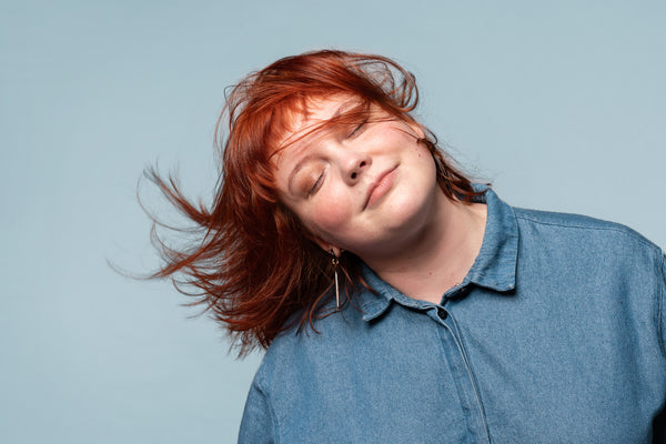 A red headed woman with her hair blowing in the wind. She is eco-chic.