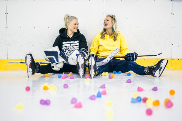 Two women ice hockey players sitting on the ice rink surrounded by menstrual cups and their ice hockey gear.