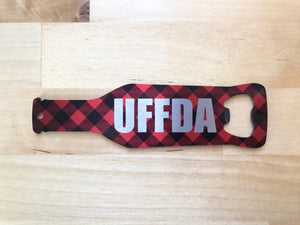 Stainless steel bottle shaped bottle opener with the word uffda and red and black check background