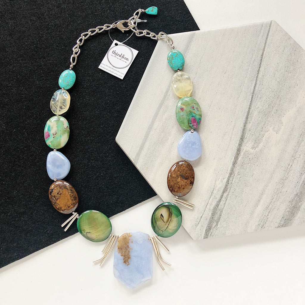 Semiprecious stone statement necklace by Third & Co. Studio handmade in Michigan with blue Chalcedony, Sterling Silver spikes, green and brown Mother of Pearl, brown Jasper, green and pink Ruby in Fuchsite. blue green Turquoise and yellow Pineapple Quartz with silver chain adjustable length
