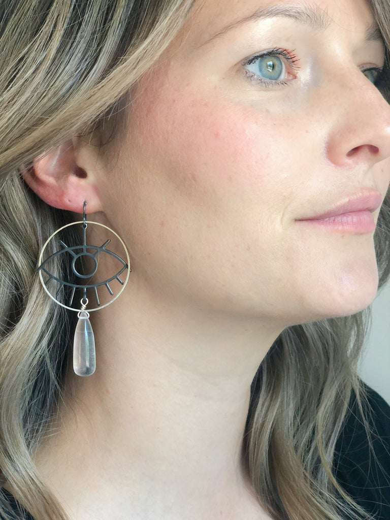 Clear Quartz teardrop with all seeing eye geometric design in matte black with silver plated open circle and oxidized sterling silver ear wires