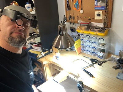 Don Wilcox - Artist sitting at his jewelry workbench