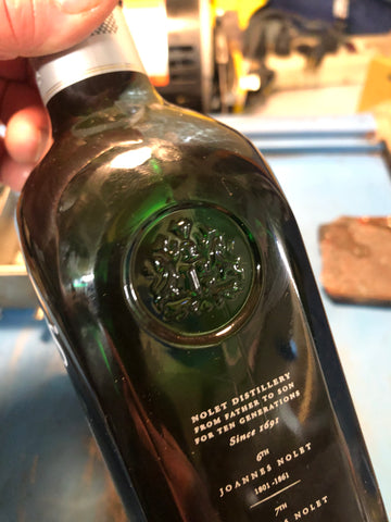 ond of two embossed coat of arm logos on a green bottle