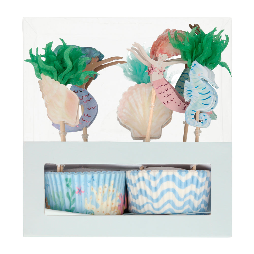 Featuring watercolor illustrations of swimming mermaids, seashells, seahorse made of paper card-stock and seaweed  made of shades of green tissue paper i  n a set of twenty four toppers and baking cases