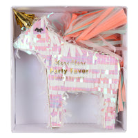 mini unicorn party favor pinata packaged in box, unicorn is made of iridescent fringe paper and has a gold unicorn horn and multicolor paper tail filled with confetti and two temporary tattoos, room for additional small treats.