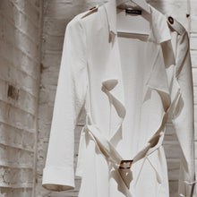 White waterfall trench coat hanging on a coat hanger outside.