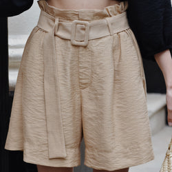 Woman wearing high waist long length beige shorts with black top.