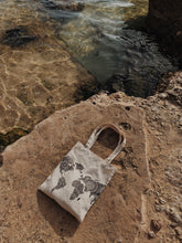 Kate World map canvas bag on a rock in the ocean.