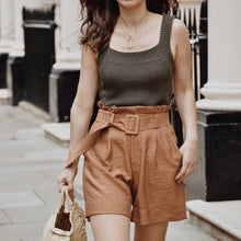 Woman wearing khaki knit top and high waist rust shorts outside.
