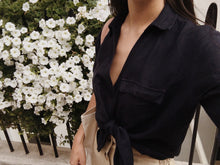 Woman wearing Navy Melissa linen shirt tied at the waist with front pocket and v neck.