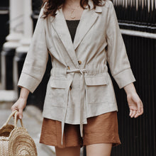 Woman wearing neutral blazer with four buttons with tie at the waist with shorts and khaki knit top.