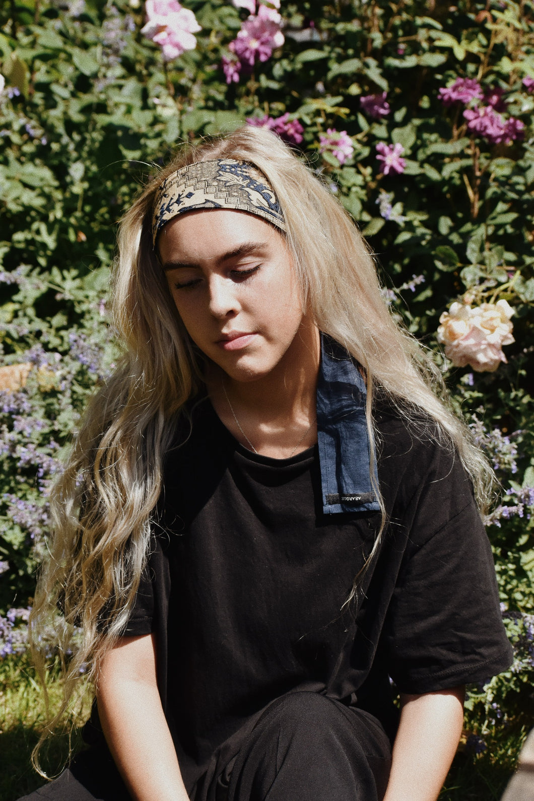 Blonde woman wearing Autumn headband outside in the garden with black t-shirt.