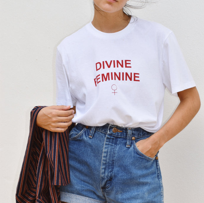 Woman wearing divine feminine t-shirt with red print with denim shorts and Ararose Charlotte shirt.