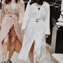 Two women wearing waterfall trench coats in nude and white.