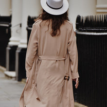 Back view of woman wearing nude waterfall trench coat with hat.