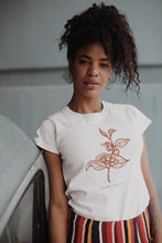 Woman wearing organic cotton and recycled plastic bottle t-shirt with orange plant print.