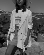 Black and white photo of woman wearing white divine feminine t-shirt with red font and white blazer.