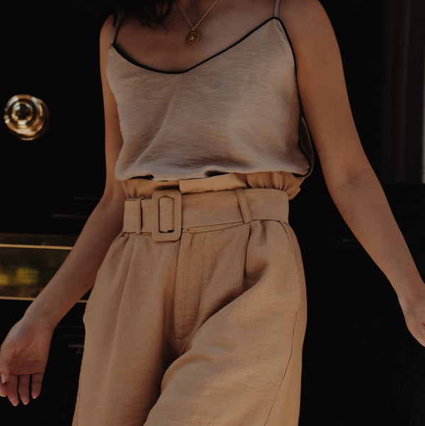 Woman wearing beige Estelle Cami top with black v neck edging and rust high waisted shorts.