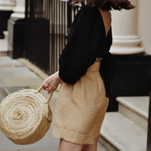 Woman wearing high waist long length beige shorts with black top and basket bag.