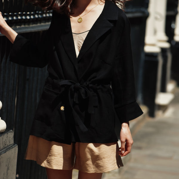 Woman wearing black blazer with four buttons with tie at the waist with shorts and cami top.