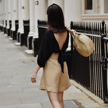 Back view of woman wearing Ararose black wrap top with beige shorts.