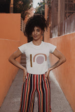 Woman wearing white organic cotton t-shirt with pink, orange and khaki abstract design and trousers.