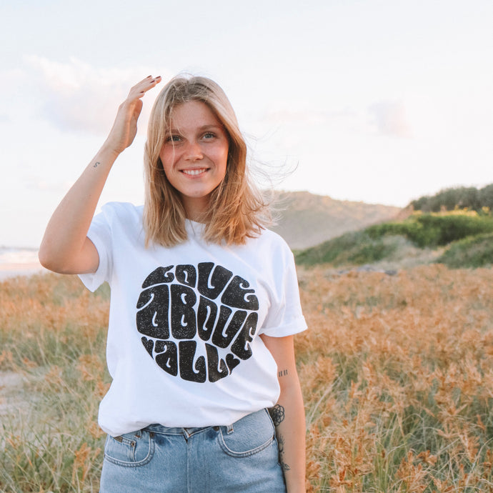 Blonde woman wearing white organic Love above all t-shirt with black print and jeans.