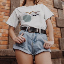 Woman wearing Carnaby's Fly Into The Sunset Organic T-shirt with denim shorts.