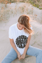 Blonde woman wearing White organic love above all t-shirt with black print and jeans in the sand.
