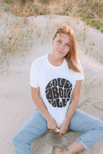 Blonde woman wearing white organic Love above all t-shirt with black print and jeans at the beach.