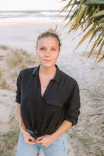 Blonde woman wearing navy Melissa linen shirt on the beach.